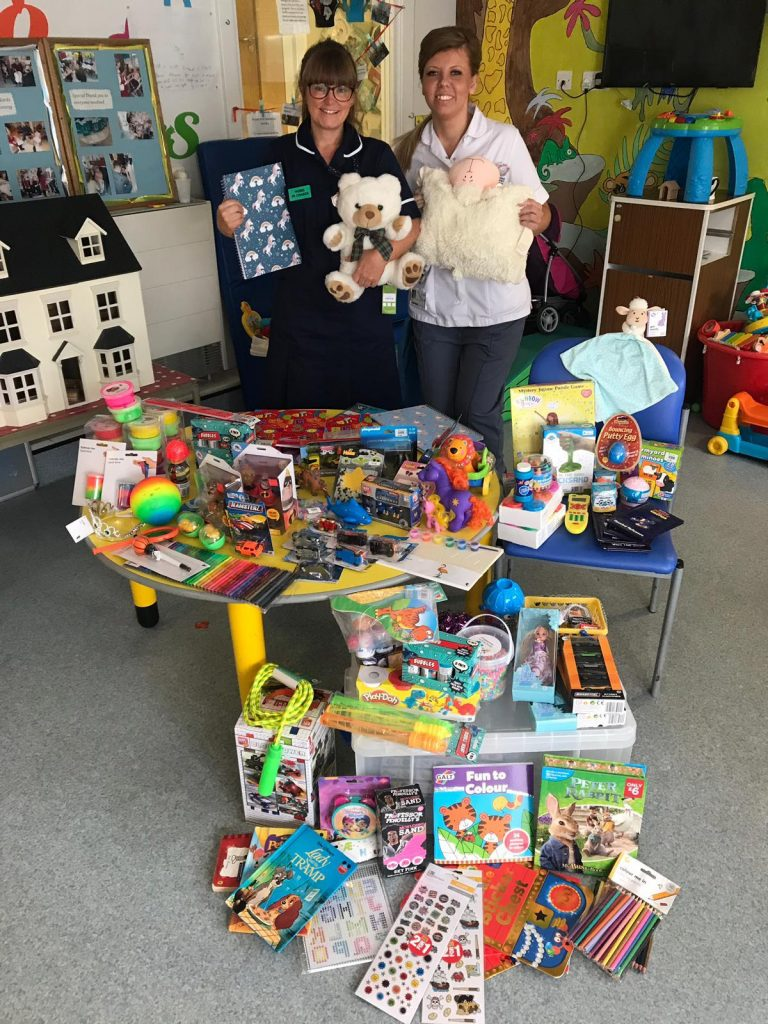 Staff at Rainbow Ward at QEQM hospital look over toys bought by Canterbury Academy pupils after fundraising during their Community Week